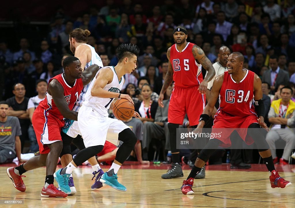 Jeremy Lin (2nd L) of the Charlotte Hornets dribbles the ball while guarded by the Los Angeles Clippers during their 2015 NBA Global Games China pre-season basketball match at the Shenzhen Universiade Center in Shenzhen, in southern China's Guangdong province on October 11, 2015. CHINA