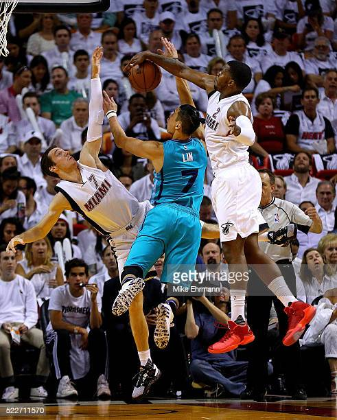 Jeremy Lin of the Charlotte Hornets is defended by Goran Dragic and Joe Johnson of the Miami Heat during game two of the Eastern Conference...