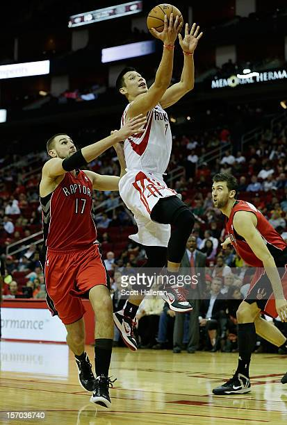 Jeremy Lin of the Houston Rockets drives past Jonas Valanciunas of the Toronto Raptors at the Toyota Center on November 27, 2012 in Houston, Texas....