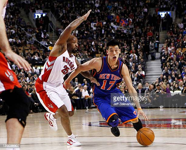 Jeremy Lin of the New York Knicks drives by Anthony Carter of the Toronto Raptors at the Air Canada Centre February 14 2012 in Toronto Ontario Canada...