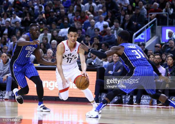 Jeremy Lin of the Toronto Raptors dribbles the ball as Jerian Grant and Terrance Ross of the Orlando Magic defend during the second half of an NBA...