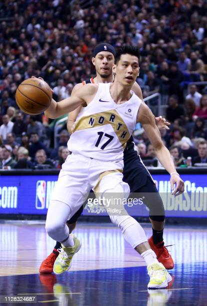 Jeremy Lin of the Toronto Raptors dribbles the ball as Seth Curry of Portland Trail Blazers defends during the first half of an NBA game against at...