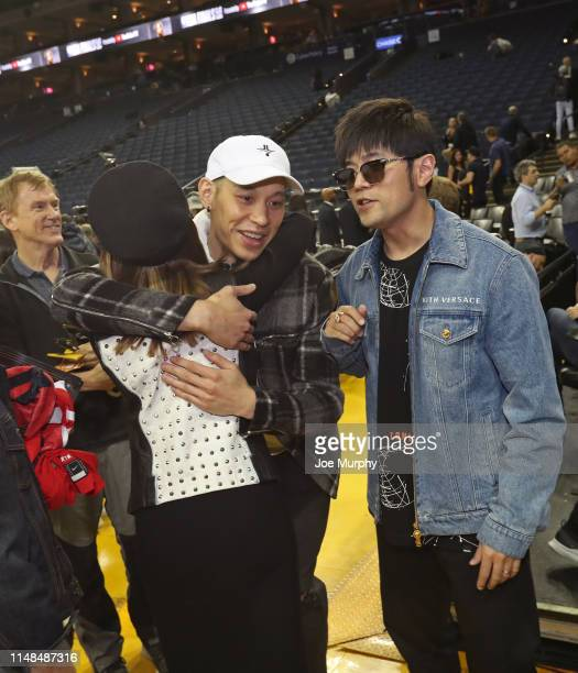 Jeremy Lin of the Toronto Raptors hugs Hannah Quinlivan and walks off the court with Jay Chou after Game Four of the NBA Finals against the Golden...