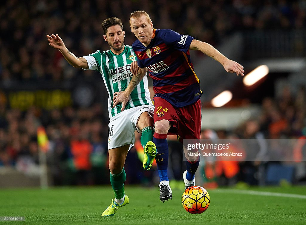 Jeremy Mathieu (24) of Barcelona is tackled by CeJudo of Betis during the La Liga match between FC Barcelona and Real Betis Balompie at Camp Nou on December 30, 2015 in Barcelona, Spain.