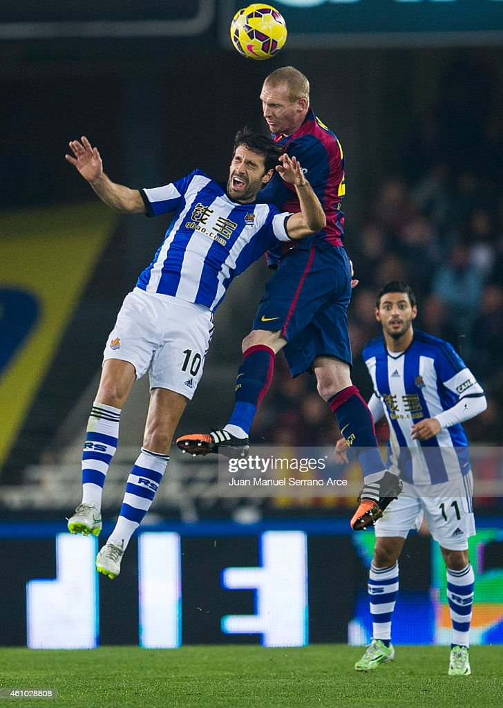 Jeremy Mathieu of FC Barcelona duels for the ball with Xabier Prieto of Real Sociedad during the La Liga match between Real Sociedad and Barcelona at Estadio Anoeta on January 4, 2015 in San Sebastian, Spain.