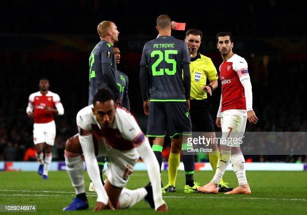 Jeremy Mathieu of Sporting CP is shown a red card by referee Gediminas Mazeika after a foul on Pierre-Emerick Aubameyang of Arsenal during the UEFA...