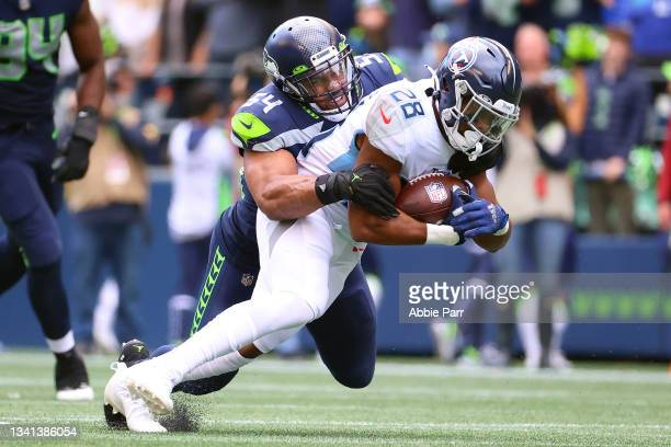 Jeremy McNichols of the Tennessee Titans is tackled by Bobby Wagner of the Seattle Seahawks during the fourth quarter at Lumen Field on September 19,...