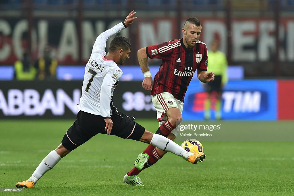 Jeremy Menez (R) of AC Milan is tackled by Achraf Lazaar of US Citta di Palermo during the Serie A match between AC Milan and US Citta di Palermo at Stadio Giuseppe Meazza on November 2, 2014 in Milan, Italy.