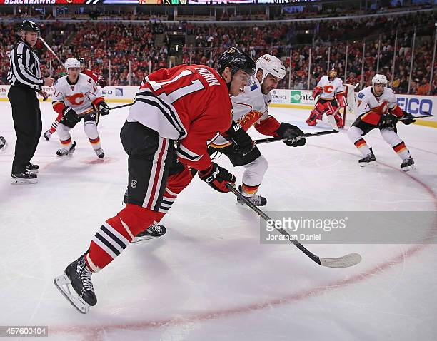 Jeremy Morin of the Chicago Blackhawks and Mark Giordano of the Calgary Flames chase the puck after a faceoff at the United Center on October 15 2014...
