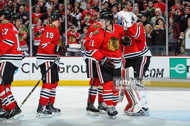 Jeremy Morin of the Chicago Blackhawks celebrates with teammates after a 32 win against the Carolina Hurricanes during the NHL game on March 21 2014...