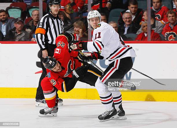 Jeremy Morin of the Chicago Blackhawks dumps Deryk Engelland of the Calgary Flames at Scotiabank Saddledome on November 20 2014 in Calgary Alberta...