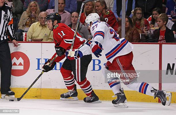 Jeremy Morin of the Chicago Blackhawks looks to pass under pressure from Ryan McDonagh of the New York Rangers during a preseason game at the United...