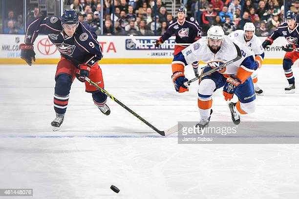 Jeremy Morin of the Columbus Blue Jackets and Nick Leddy of the New York Islanders chase after a loose puck on January 10 2015 at Nationwide Arena in...
