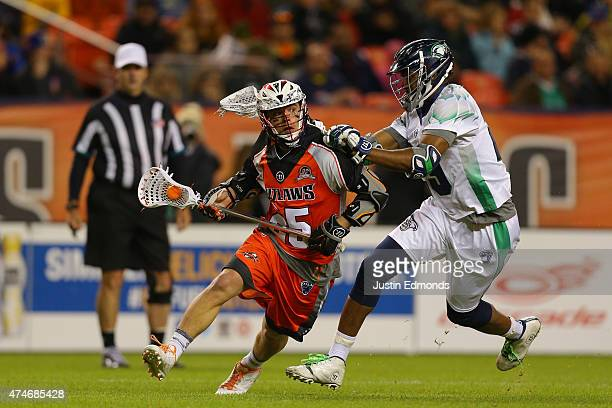 Jeremy Noble of the Denver Outlaws drives against Mark McNeill of the Chesapeake Bayhawks during the fourth quarter at Sports Authority Field at Mile...