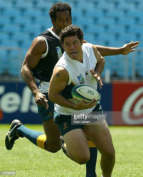 Jeremy Paul runs with Lote Tuqiri giving chase during the Australian Wallabies Captain's Run on November 14, 2003 at Telstra Stadium in Sydney,...