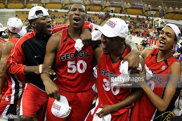 Jeremy Price, Terrance Woodbury and other members of the Georgia Bulldogs celebrate after defeating the Arkansas Razorbacks 66-57 during the...