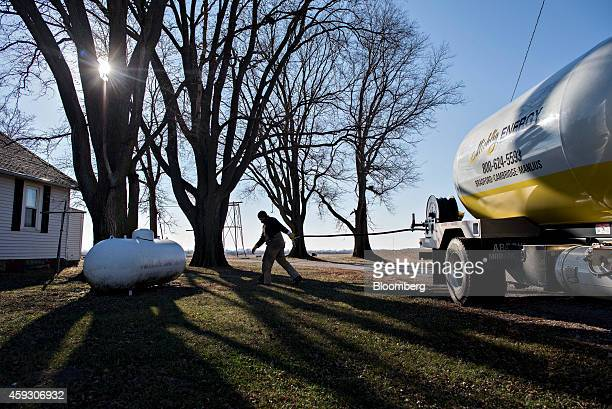 Jeremy Rediger a propane delivery driver for Michlig Energy pulls a hose toward a propane tank while making a delivery outside Annawan Illinois US on...