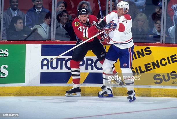 Jeremy Roenick of the Chicago Blackhawks is checked into the boards by Guy Carbonneau of the Montreal Canadiens during an NHL game circa 1990 at the...