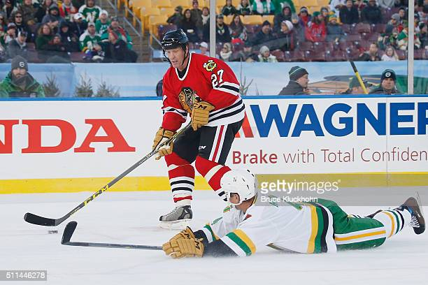 Jeremy Roenick of the Chicago Blackhawks skates with the puck as Craig Hartsburg of the Minnesota Wild makes a diving defensive play during the Coors...