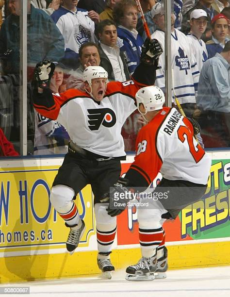Jeremy Roenick of the Philadelphia Flyers celebrates his gamewinning goal at 1221 of the first overtime period with teammate Marcus Ragnarsson...