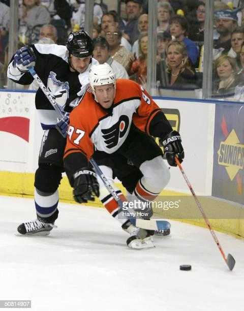 Jeremy Roenick of the Philadelphia Flyers tries to get to the puck while Nolan Pratt of the Tampa Bay Lightning trips him up during Game one of the...