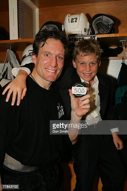 Jeremy Roenick of the San Jose Sharks and his son pose with the puck that gave him 500 career goals after a NHL game against the Phoenix Coyotes on...