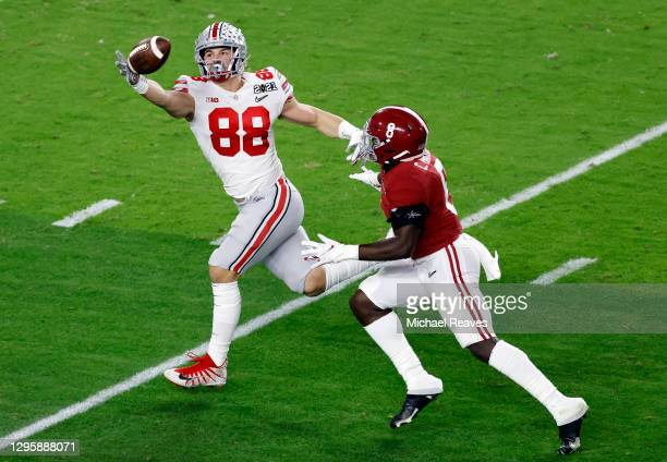 Jeremy Ruckert of the Ohio State Buckeyes reaches for a catch ahead of Christian Harris of the Alabama Crimson Tide during the first quarter of the...