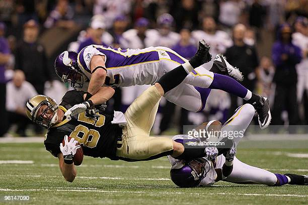 Jeremy Shockey of the New Orleans Saints gets tackled by Chad Greenway and Antoine Winfield of the Minnesota Vikings after catching a pass for a...