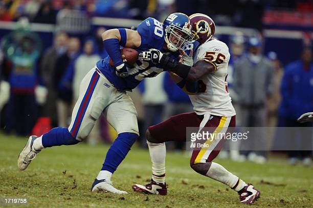 Jeremy Shockey of the New York Giants is wrapped up by LaVar Arrington of the Washington Redskins during the NFL game at Giants Stadium on November...