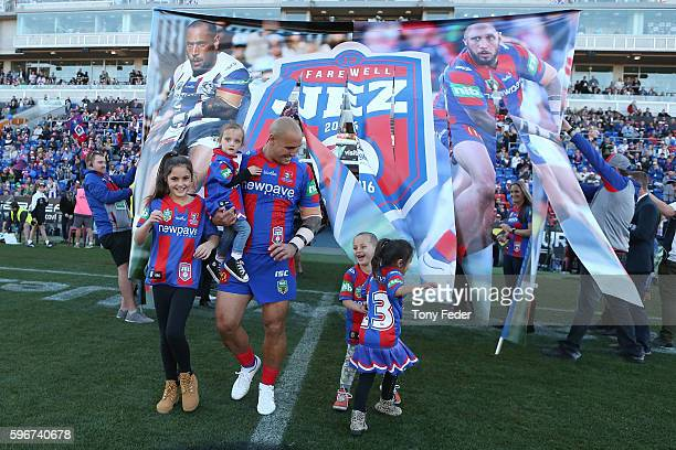 Jeremy Smith with his family runs through the banner before playing his last game at home for the Knights during the round 25 NRL match between the...
