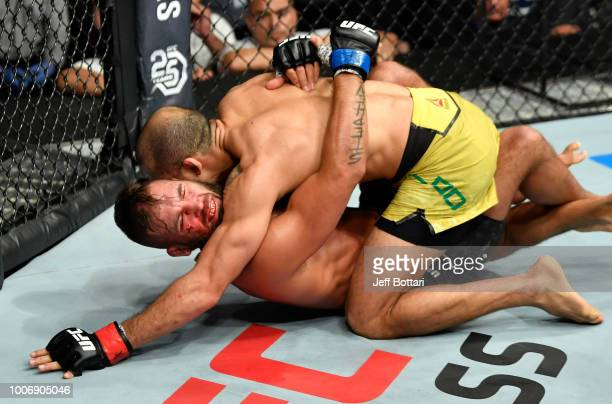 Jeremy Stephens cringes in pain after being dropped by a body shot from Jose Aldo of Brazil in their featherweight bout during the UFC Fight Night...