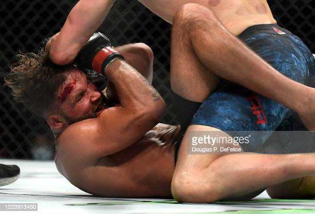 Jeremy Stephens of the United States covers up on the ground against Calvin Kattar of the United States in their Featherweight fight during UFC 249...