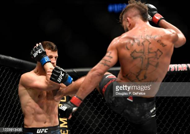 Jeremy Stephens of the United States kicks Calvin Kattar of the United States in their Featherweight fight during UFC 249 at VyStar Veterans Memorial...