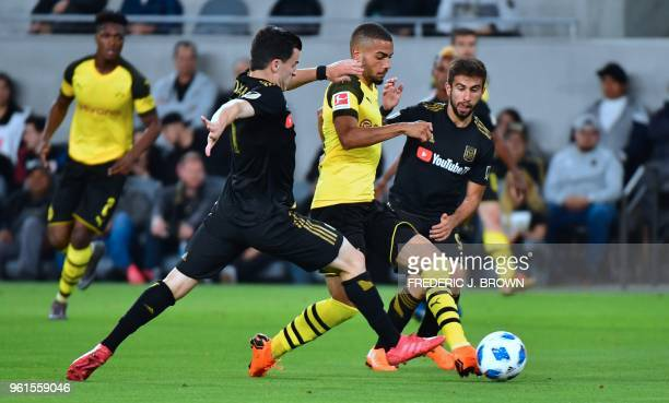 Jeremy Toljan of Borussia Dortmund vies for the ball with Diego Rossi and Aaron Kovar of LAFC during their international soccer friendly in Los...