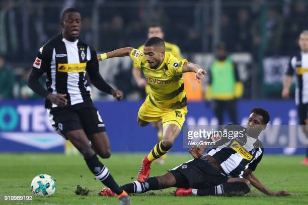 Jeremy Toljan of Dortmund is challenged by Reece Oxford and Denis Zakaria of Moenchengladbach during the Bundesliga match between Borussia...