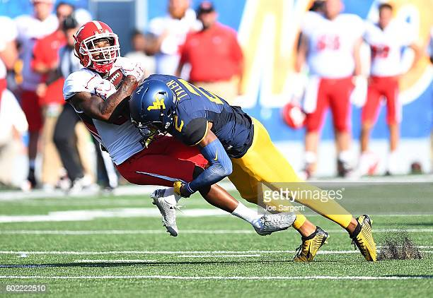 Jeremy Tyler of the West Virginia Mountaineers knocks the ball loose on a catch attempt by Alvin Bailey of the Youngstown State Penguins during the...