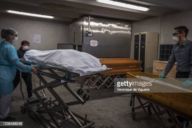 Jeremy Walter, an undertaker, right, prepares to place the body of an elderly COVID-19 victim into a coffin at the Saint Morand hospital morgue on...