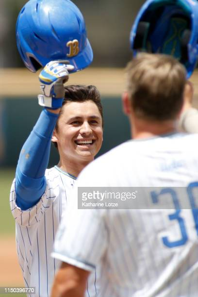 Jeremy Ydens of UCLA tips his helmet with teammate Jake Pries of UCLA following a home run during a baseball game against University of Washington at...