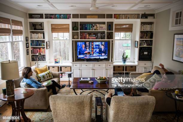 Jeremy Zeitler right watches tv with his parents Jon Zeitler and Cynthia Baker at home on Saturday March 17 in Washington DC With thousands of people...