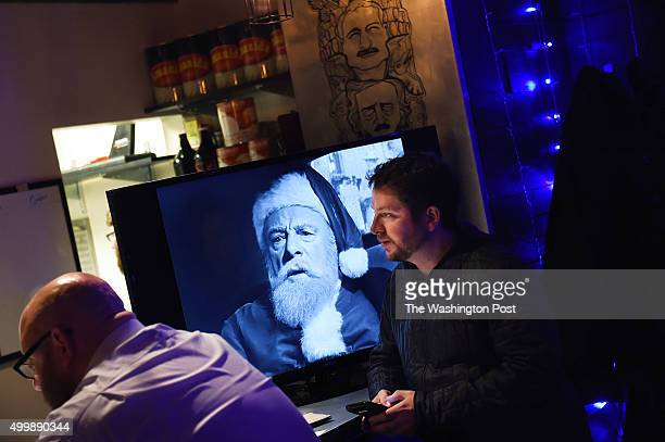 """Jeremy Zunk, right, sits next to a television screen with the Christmas movie, """"Miracle on 34th Street"""" at the holiday themed bar, Miracle on Seventh..."""
