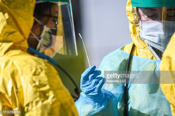 A cotton swab used in a nasal passage as health care professionals test for COVID19 at the ProHEALTH testing site in Jericho New York on March 24 2020