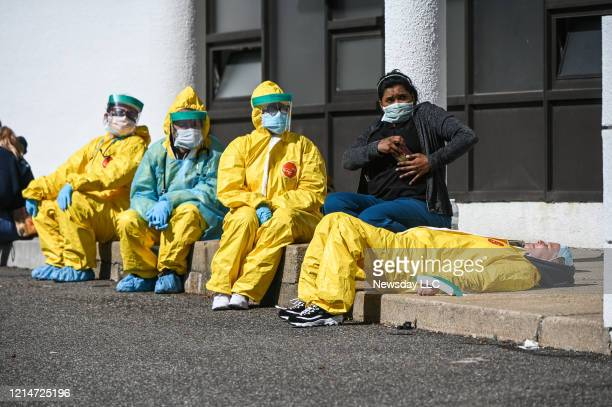 Health care professionals take a break awaiting patients as they test for COVID-19 at the ProHEALTH testing site in Jericho, New York, March 24, 2020.