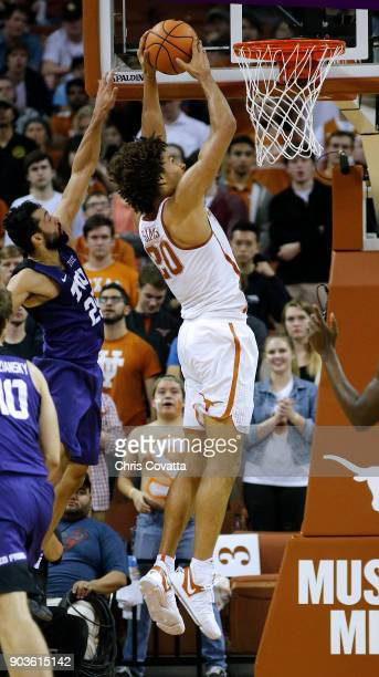 Jericho Sims of the Texas Longhorns dunks and gets fouled by Alex Robinson of the TCU Horned Frogs at the Frank Erwin Center on January 10 2018 in...
