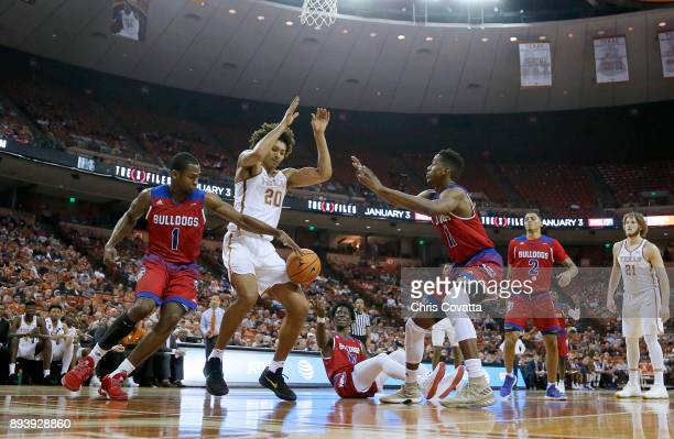 Jericho Sims of the Texas Longhorns looses the ball as he is surrounded by Derric Jean Anthony Duruji and JaColby Pemberton of the Louisiana Tech...