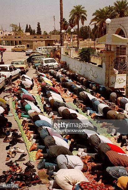 Moslem Palestinians block Jericho's main road 06 May 1994 as they kneel outside the overcrowded mosque for the first Friday noon prayer since this...