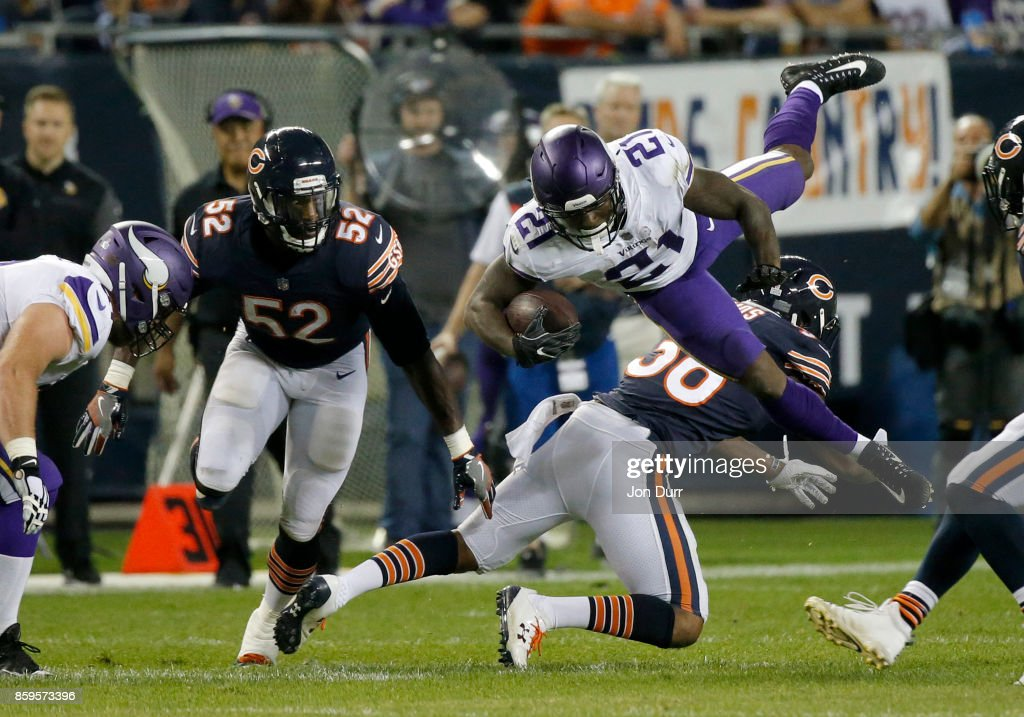 Jerick McKinnon #21 of the Minnesota Vikings is hit by Adrian Amos #38 of the Chicago Bears in the second quarter at Soldier Field on October 9, 2017 in Chicago, Illinois.