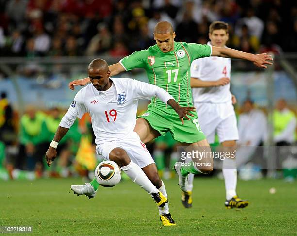Jermain Defoe of England challenged by Adlane Guedioura of Algeria during the 2010 FIFA World Cup South Africa Group C match between England and...