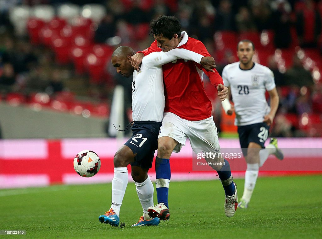 Jermain Defoe of England holds off Marcos Gonzalez of Chile during the international friendly match between England and Chile at Wembley Stadium on November 15, 2013 in London, England.