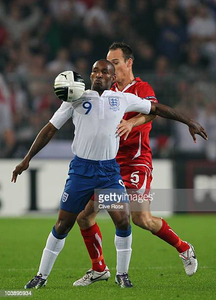 Jermain Defoe of England is challenged by Steve von Bergen of Switzerland during the UEFA EURO 2012 Group G Qualifier between Switzerland and England...