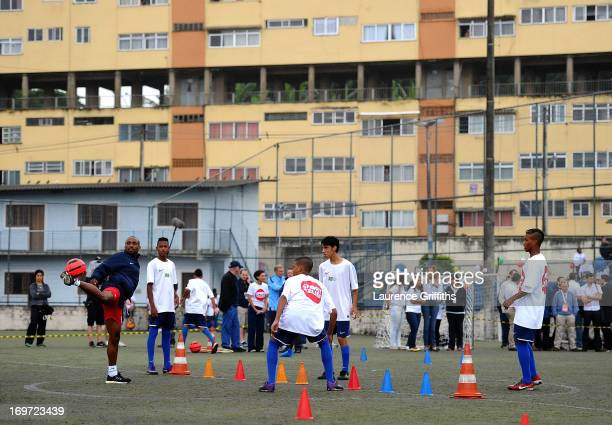 Jermain Defoe of England joins in a training session for local children during a visit to a Sport Relief project on May 31 2013 in Rio de Janeiro...